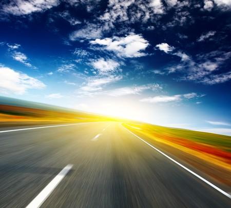 autopista: Carretera asfaltada borrosa y cielo azul con nubes y terreno de luz