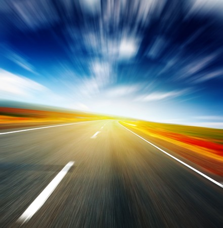 side of light: Blurred asphalt road and blue motion blurred sky with clouds and light spot