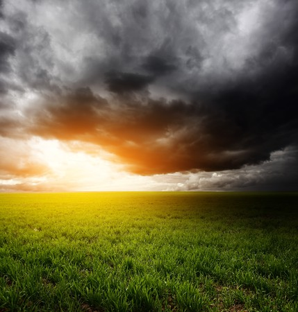 dark cloud: Storm dark clouds and light over field with green grass