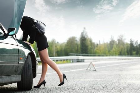 Young woman weared heels repairing her broken car photo