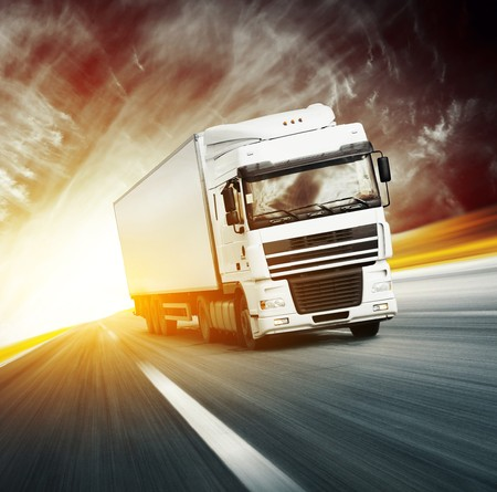 lorry: White truck on asphalt blurry road and abstract red sky with clouds ans sun
