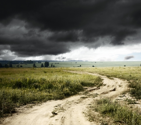 dark jungle green: Road in field and storm clouds