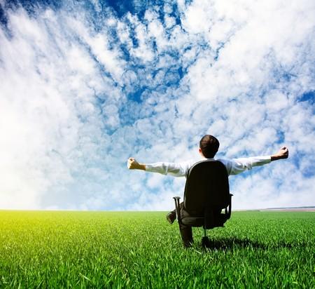 simplicity: Hombre con las manos levantadas sentado en la silla en el Prado verde