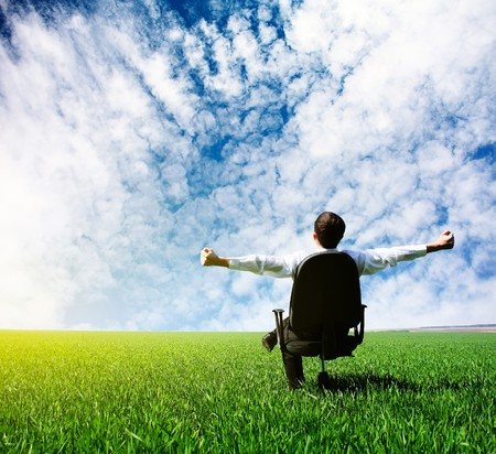 and simplicity: Man with raised hands sitting on chair on green meadow Stock Photo