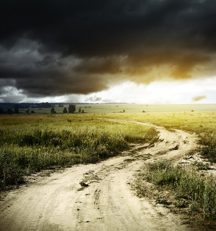 dark cloud: Road in field and storm clouds