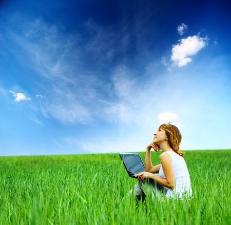 Mujer con portátil sentado en el Prado verde y mirando a un cielo  Foto de archivo