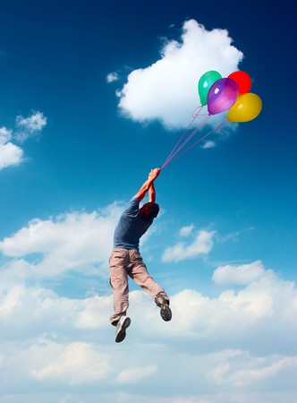 Young man flying in blue sky holding group of collored ballons