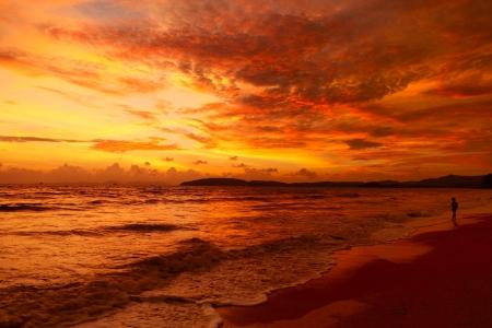 Alone man walking on beach under sunset Stock Photo