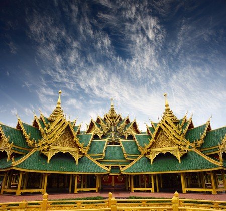 Golden roof of a temple and blue sky with clouds photo