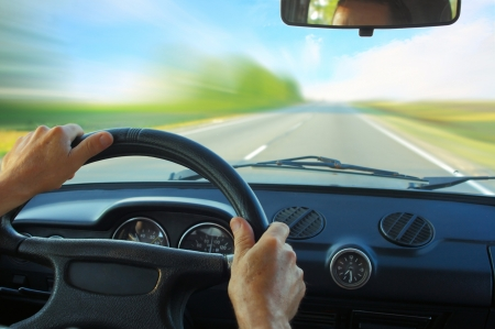 dash: Driver in car holding steering wheel. Blurred road and sky Stock Photo
