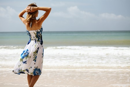 Young woman in dress standing on sand and looking to a sea photo