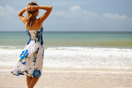 Jonge vrouw in jurk permanent op zand en op zoek naar een zee