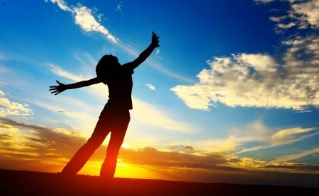夕焼けの草原の上に立って上げられた手を持つ若い女