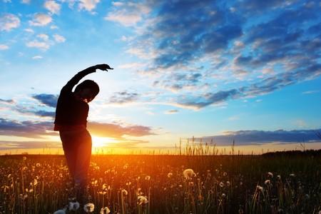 夕日にハーブと草原に立っている若い女性