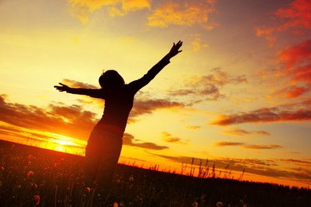 puesta de sol: Mujer joven con las manos levantadas de pie en la pradera con hierbas en la puesta de sol  Foto de archivo