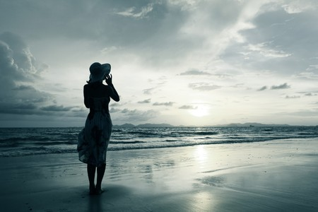 look: Young woman in hat standing on sand and looking to a sunset