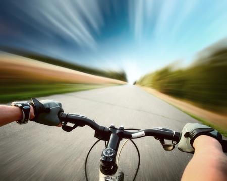 ciclismo: Jinete de la conducci�n de bicicleta por una carretera asfaltada. Fondo de movimiento borrosa Foto de archivo