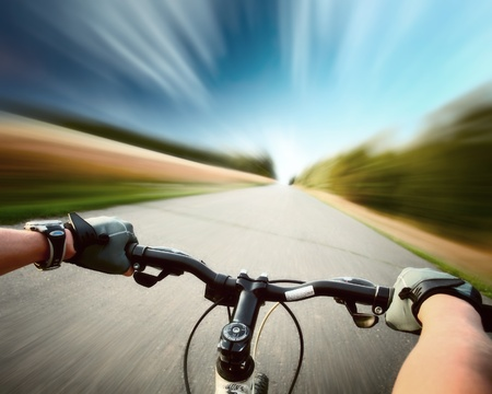 Rider driving bicycle on an asphalt road. Motion blurred background Stock Photo - 8333203