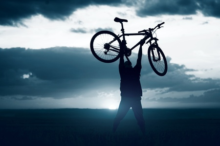rear wheel: Man with bicycle lifted above him Stock Photo
