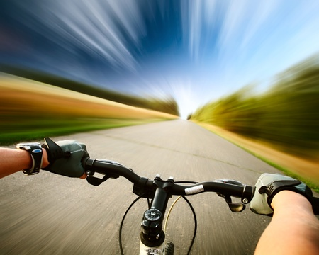 Rider driving bicycle on an asphalt road. Motion blurred background photo