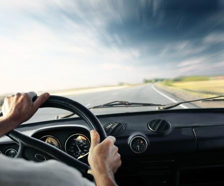 manejando: Conductor de manos en un volante de un coche y un cielo azul con nubes borrosas