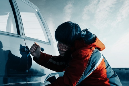 Young man breacking door of a car photo