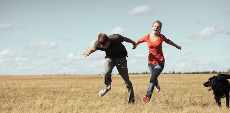 Young pair running on meadow with a dog Stock Photo - 8323331