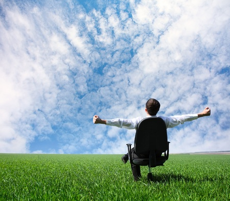 Man with raised hands sitting on chair on green meadow Stock Photo - 8323341