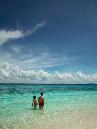 swimm: Young pair walking walking on beach and going to swimm