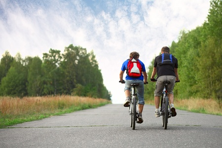bicyclists: Two young guys on bicycles riding together on an asphalt road