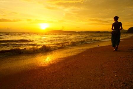 Joven caminando por la playa bajo la luz de la puesta del sol Foto de archivo