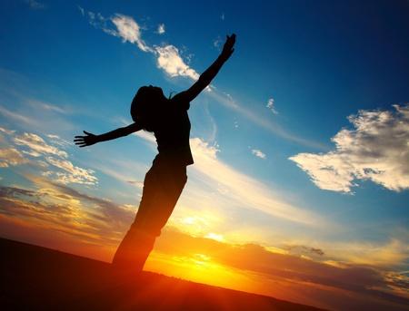 manos levantadas al cielo: Mujer joven con las manos levantadas pie en tierra sobre el atardecer luz