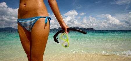 Young woman with wet skin and with a mask standing on sand after snorkelling in clear sea photo
