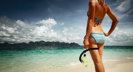 Young woman with wet skin and with a mask standing on sand and going to snorkelling in clear sea photo