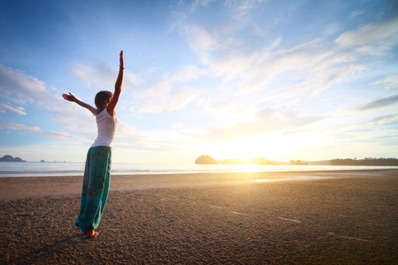 Young woman with raised hands standing on sand and looking to a sky photo