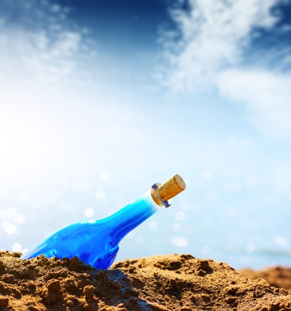 Blue empty bottle in coast sand and blue sky with clouds photo