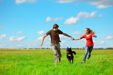 Young happy lovers runnung with a dog on meadow with green grass and blue sky Stock Photo - 8581130