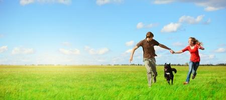 disfrutar: Runnung de j�venes amantes feliz con un perro en la pradera con pasto verde y el cielo azul Foto de archivo