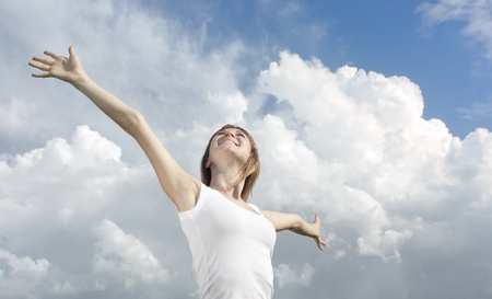 enjoy space: Smiling young woman in white shirt on cloudy sky background