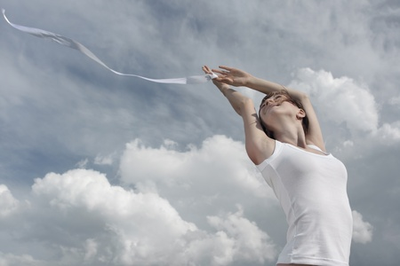 enjoy space: Smiling young woman in white shirt with white ribbon on cloudy sky background Stock Photo