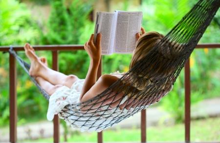 mujer leyendo libro: Mujer joven leyendo un libro en una hamaca Foto de archivo