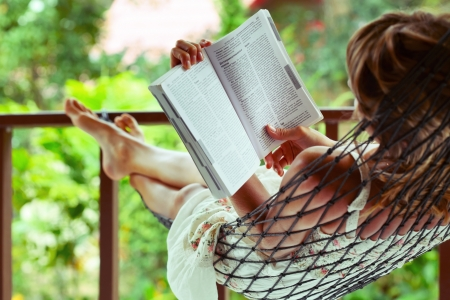 Young woman reading a book lying in a hammock Stockfoto