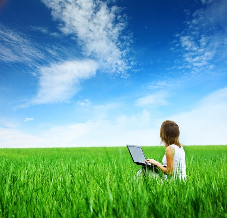 Young Woman with Laptop sitting on green Grass and looking um eine blue cloudy sky