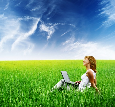 Young woman with laptop sitting on green grass Stock Photo - 8581058