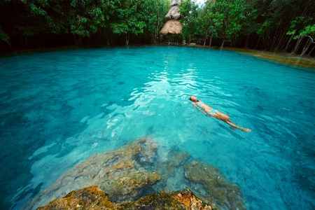 Young woman swimming alone in a blue clear water of a lake situated in tropical forest Stock Photo - 8581074