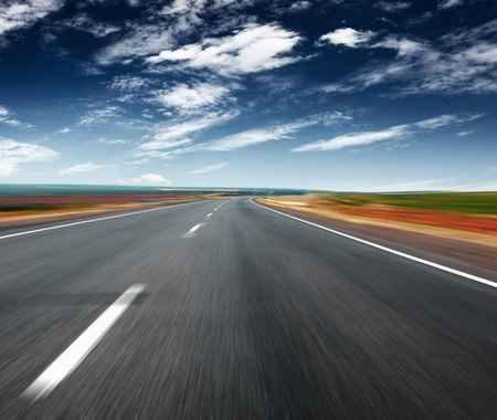 Asphalt blurred road and blue sky with clouds photo