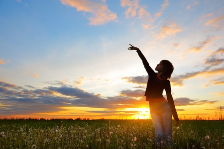 pointing herbs: Young woman standing on meadow with herbs and pointing to a sky Stock Photo