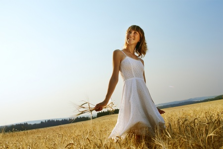 Smiling woman in white dress walking on field with ripe yellow wheat photo