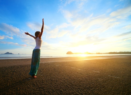 Young woman with raised hands standing on wet sand and looking to a sky photo