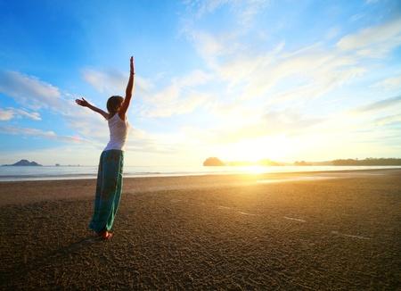 Mujer joven con las manos levantadas de pie en la arena mojada y mirando a un cielo